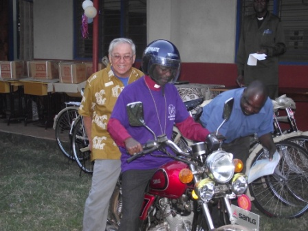 Bishop Mwita on a test ride of  donated motorcyle